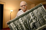 Foto de l'autor. Sitchin posing with with an enlarged, purported 6000-year-old cylinder seal impression [credit: Lapavaestacaliente of Wikipedia]