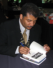 "Author photo. Neil deGrasse Tyson siging a copy of his book ""Origins"". Portrait taken at JREF's TAM6, The Amazing Meeting. Photo by Wikimedia Commons user Sgerbic"