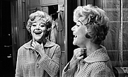 Author photo. Dora Bryan smiles into her dressing room mirror after having to leave a show because of a sore throat, in 1966.