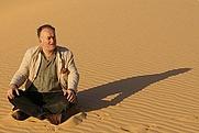 Author photo. Barnaby Rogerson outside the Saharan fortress of Bou Njem, in the Libyan desert (photograph © Don Mcullin)