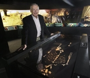"""Author photo. Dr. Donald Johanson, founding director of the Institute of Human Origins at Arizona State University, poses with his discovery, the 3.2 million-year-old Lucy skeleton, part of the """"Lucy's Legacy: The Hidden Treasures of Ethiopia"""" exhibit at the Discovery Times Square Exposition in New York, Wednesday June 24, 2009."""