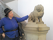 Author photo. Jo Walton trying to cheer up a stone lion in Florence.