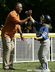 Author photo. A player from the District 12 Little League Challengers of Williamsport, Pa., is given a high-five from baseball star Ozzie Smith, Sunday, July 24, 2005, during a Tee Ball game on the South Lawn of the White House. White House photo by Paul Morse