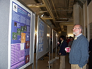 """Author photo. David Malin looking at a poster about Malin 1, the first galaxy to be discovered by him [credit: Catherine """"Sailor Coruscant""""]"""