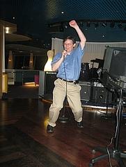 Author photo. John Rennie hits the karaoke mike. Photo by Flickr user Randal Schwartz