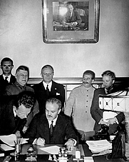 Author photo. Moscow, August 23, 1939: Molotov signs the German–Soviet non-aggression pact as Ribbentrop and Stalin look on. (defenseimagery.mil)