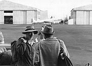 Author photo. J. Desmond Clark talking with a colleague at an airport near Dakar, Senegal (West Africa) by Wikipedia user gbaku.