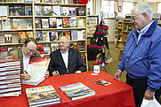 Author photo. By Lawrence Giberson: Retired Marine Cols. H. Avery Chenoweth, left, and Brooke Nihart, center, sign a copy of their book, 'Semper Fi: The definitive History of the U.S. Marines'.