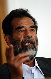 Author photo. Former President of Iraq, Saddam Hussein, makes a point during his initial interview by a special tribunal, where he is informed of his alleged crimes and his legal rights, 7/1/2004. (defenseimagery.mil)