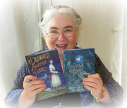 Author photo. Laura Amy Schlitz holding her latest books, A Drowned Maiden's Hair and A Night Fairy. At the 2010 Baltimore Book Festival. ©2010