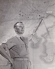 Author photo. Haywood S. Hansell, Jr. pointing to a map of Tokyo in November 1944 [credit: 21st Bomber Command]