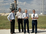 Author photo. On Oct. 9, 1986, at Kennedy Space Center, Gene Thomas, director of launch and landing operations, stands in front of shuttle Atlantis on launch pad 39B. To Thomas' right are Bill Warren, pad site manager; Bob Sieck, director of shuttle management and operations; and Lt. Gen. Forrest McCartney, KSC director.