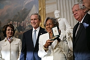 Author photo. Rachel Robinson accepts the Congressional Gold Medal on behalf of her husband Jackie Robinson during a ceremony at the U.S. Capitol, Wednesday, March 2, 2005. Pictured, from left, are Nancy Pelosi, President Bush, Rachel Robinson and Dennis Hastert.