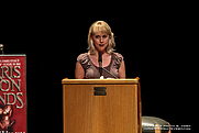Author photo. Giving a talk about perseverance in the publishing world on stage at the Allen, TX Library, June 2012.