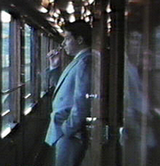 Author photo. American author, journalist and poet David M. Alexander having a smoke on the Venice-Simplon Orient Express. By Datawatch. - Own work., Public Domain, <a href=&quot;https://commons.wikimedia.org/w/index.php?curid=14515146&quot; rel=&quot;nofollow&quot; target=&quot;_top&quot;>https://commons.wikimedia.org/w/index.php?curid=14515146</a>