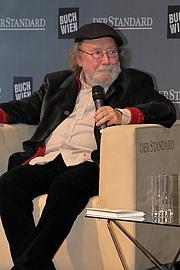"""Author photo. Der österreichischer Schriftsteller, Journalist und Musiker Peter Henisch bei der Präsentation seines Buches """"Siebeneinhalb Leben"""" auf der Standard-Bühne der Wiener Buchmesse 2018. By Bwag - Own work, CC BY-SA 4.0, <a href=""""https://commons.wikimedia.org/w/index.php?curid=74422748"""" rel=""""nofollow"""" target=""""_top"""">https://commons.wikimedia.org/w/index.php?curid=74422748</a>"""