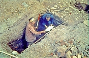 Author photo. Lady Aileen Fox down a trench (and holding a ranging rod and a trowel) in Exeter in the 1960s with an assistant [credit: Royal Albert Memorial Museum & Art Gallery, Exeter]