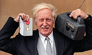 Author photo. Baylis with his CBE and one of his wind-up radios.