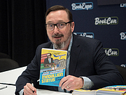 """Foto do autor. John Hodgman at BookExpo at the Javits Center in New York City, May 2019. By Rhododendrites - Own work, CC BY-SA 4.0, <a href=""""https://commons.wikimedia.org/w/index.php?curid=79387555"""" rel=""""nofollow"""" target=""""_top"""">https://commons.wikimedia.org/w/index.php?curid=79387555</a>"""