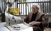 Forfatter foto. John Morris looking at Robert Capa pictures from D-day during an interview in Paris in 2014.
