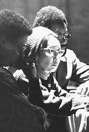 Forfatter foto. Photo credit unknown. Yuri Kochiyama sits between two men. She wears a tuque and her iconic glasses.