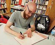Fotografia de autor. Jacob Grant signing a book at City Lit Books 06/01/19.