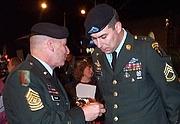 "Fotografia de autor. Sgt. Major Jack Tilley (left) talks with Sgt. 1st Class Matt Eversmann at the Washington film premiere of ""Black Hawk Down"" Jan. 15, 2002. Photo by Linda D. Kozaryn (defense.gov)"