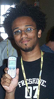 """Foto de l'autor. """"Aaron McGruder, at the 2002 Hackers On Planet Earth hacker con"""" by Rob Vincent."""