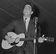 Foto do autor. Alan Lomax playing guitar on stage at the Mountain Music Festival, Asheville, North Carolina: Library of Congress Prints and Photographs Division, Lomax Collection (REPRODUCTION NUMBER:  LC-DIG-ppmsc-00433) (cropped)