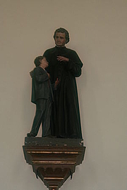 Foto do autor. St. John Bosco and Youth, Franziskanerkloster Innichen, Innichen, S. Tyrol, Italy.  Image by user JJ55 / Wikimedia Commons.